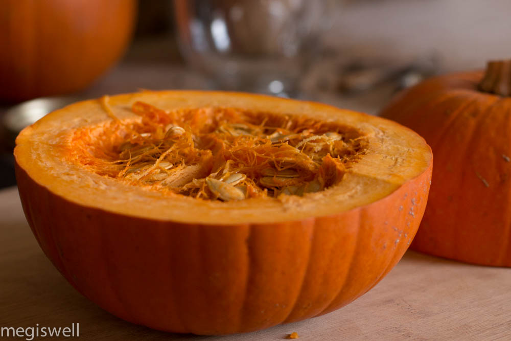 Cut the pumpkin in half, exposing the gooey guts for making a fresh pumpkin chai tea latte