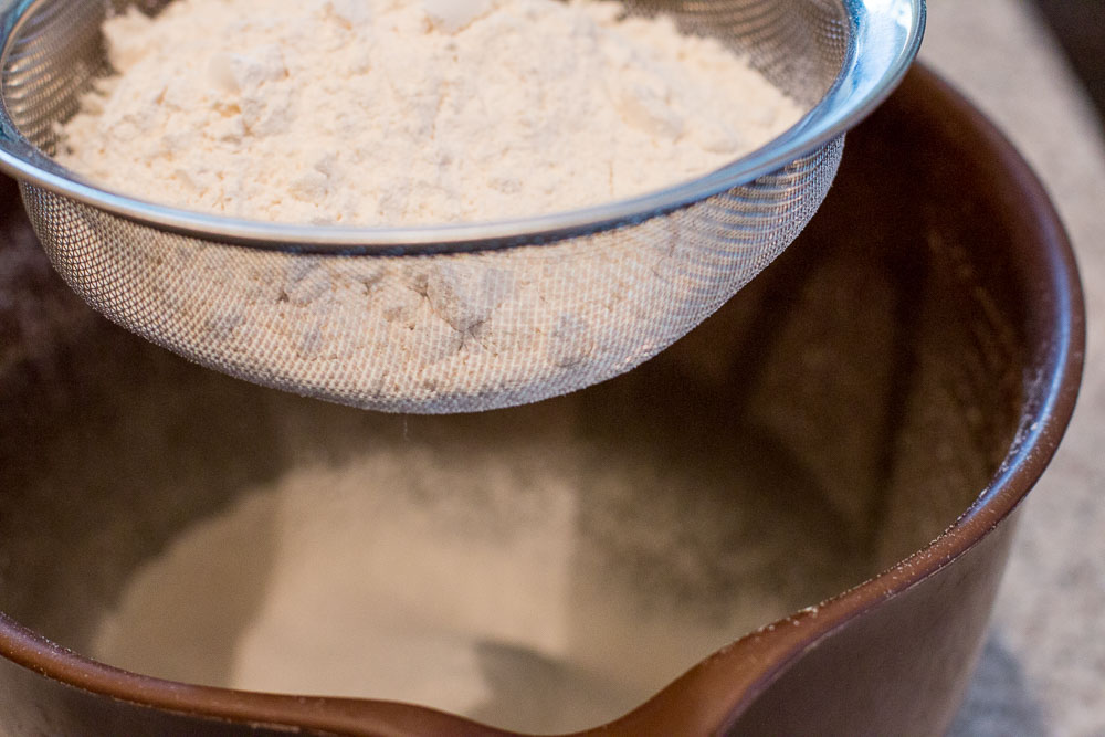 Shifting flour into a large bowl