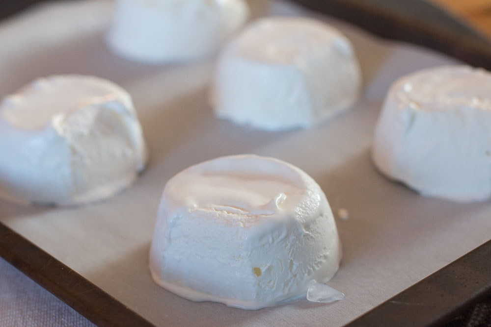 Ice cream sandwich fillings popped out of the muffin tins, placed on parchment paper, and returned to the freezer
