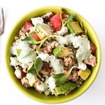 Quinoa Salmon Bowl. Quinoa, salmon, diced tomatoes & avocado, sunflower sprouts, crumbled feta cheese, and a Mixed Herb Greek Yogurt dressing make a high protein, filling, and healthy meal with great flavors and textures.