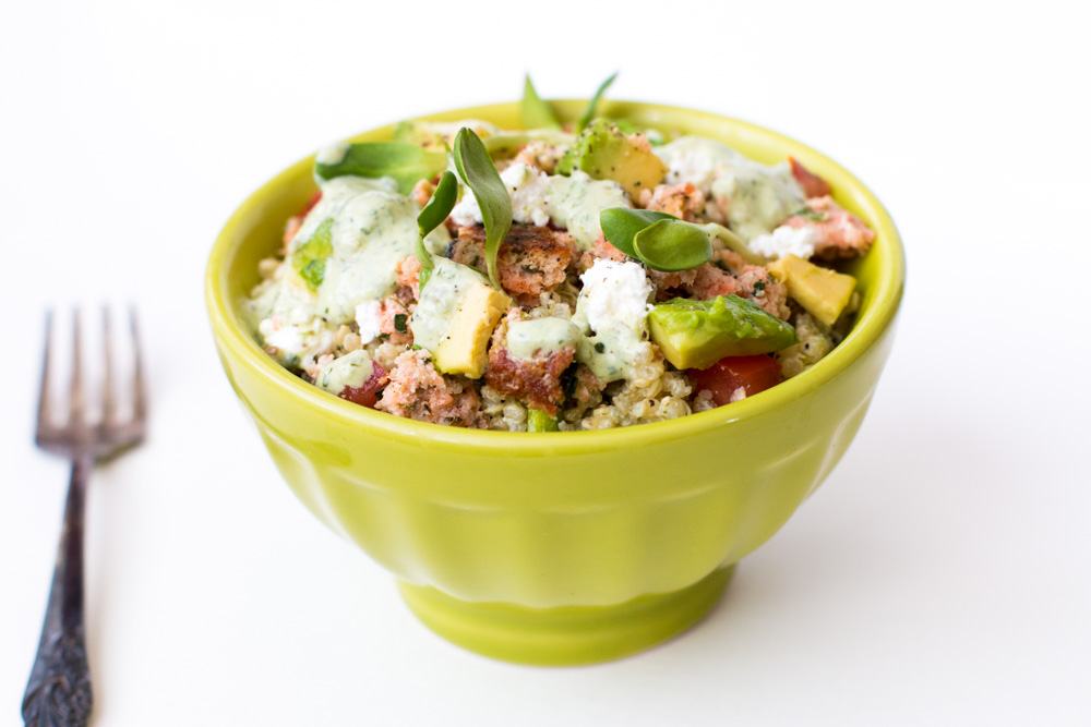 This Salmon Quinoa Bowl contains tomatoes, avocado, sunflower sprouts, feta, and a Mixed Herb Greek Yogurt dressing to make a high protein, filling, and healthy meal with great flavors and textures. | www.megiswell.com