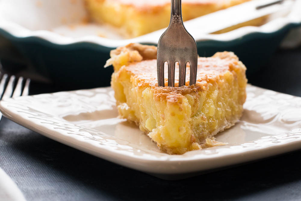Side shot view of a fork stuck in a slice of Lemon Chess Pie on a plate.