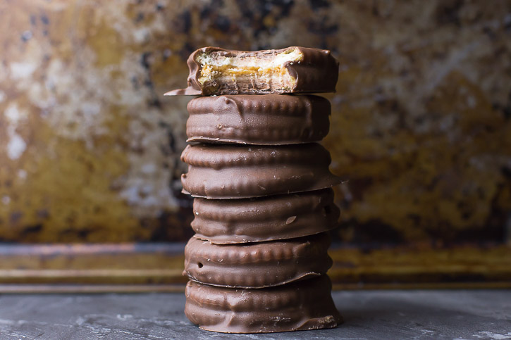 A stack of Ritz Cracker Chocolate Peanut Butter Cookies with a bite out of one.