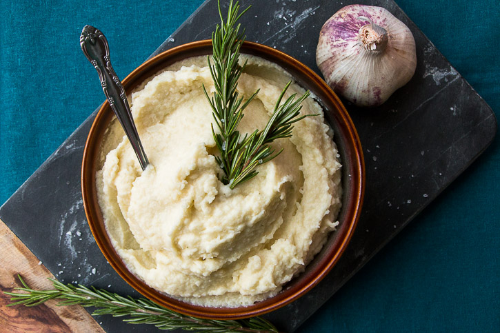 Over head shot of cauliflower potato mash in a bowl with a spoon and two sprigs of rosemary in it, on top of a cutting board surrounded by a head of garlic and rosemary.