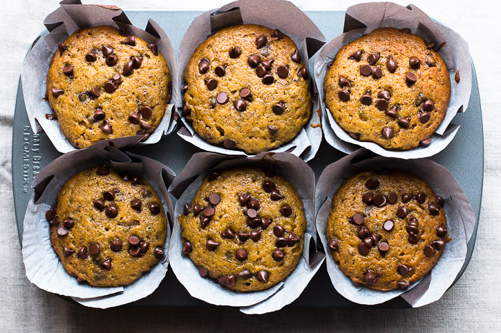 My favorite pumpkin bread recipe gets revamped in these Pumpkin Muffins with Chocolate Chips and Tahini Glaze. The tahini glaze adds a little savory goodness and pairs amazingly with the chocolate chips, creating savory-sweet muffin greatness! | www.megiswell.com