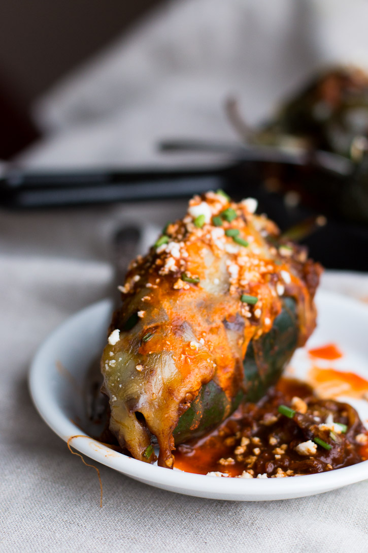 Use your leftover turkey (or chicken) in these Turkey Enchilada Stuffed Poblano Peppers. Turkey and brown rice are smothered in a homemade red enchilada sauce and topped with melty cheese. | www.megiswell.com