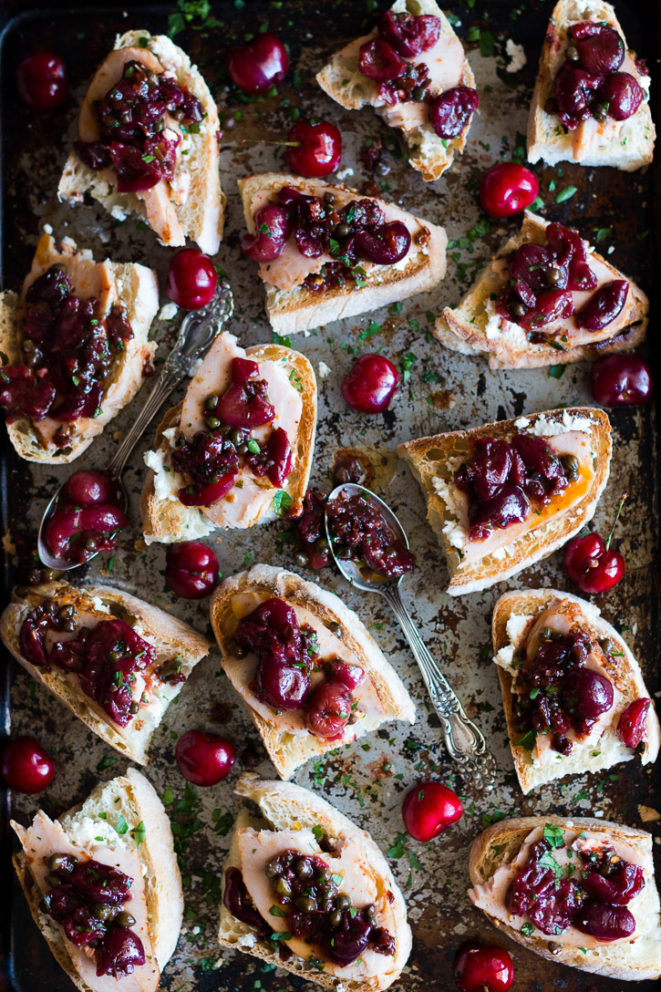 Overhead shot of a baking sheet scattered with cherries, two sauce covered spoons, and bread with sliced turkey and a roasted cherry caper sauce.
