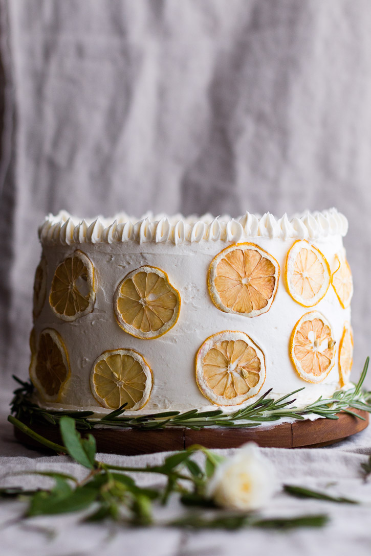 This light and classic Rosemary Sponge Cake is layered with rosemary infused apricot compote and white chocolate buttercream frosting. Dehydrated lemons and rosemary make decoration easy and beautiful. | www.megiswell.com