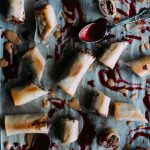 baked Duck Spring Rolls laid out on a parchment covered baking sheet with a spoon and peanut and plum sauce splattered everywhere