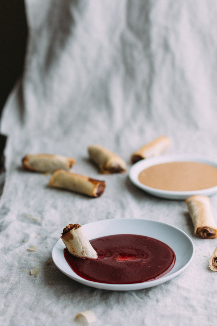 baked Duck Spring Roll dipped in plum sauce on a plate