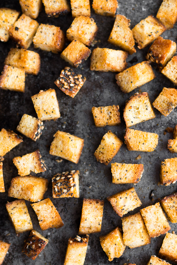 Baked and crunchy croutons laid out on a baking sheet.