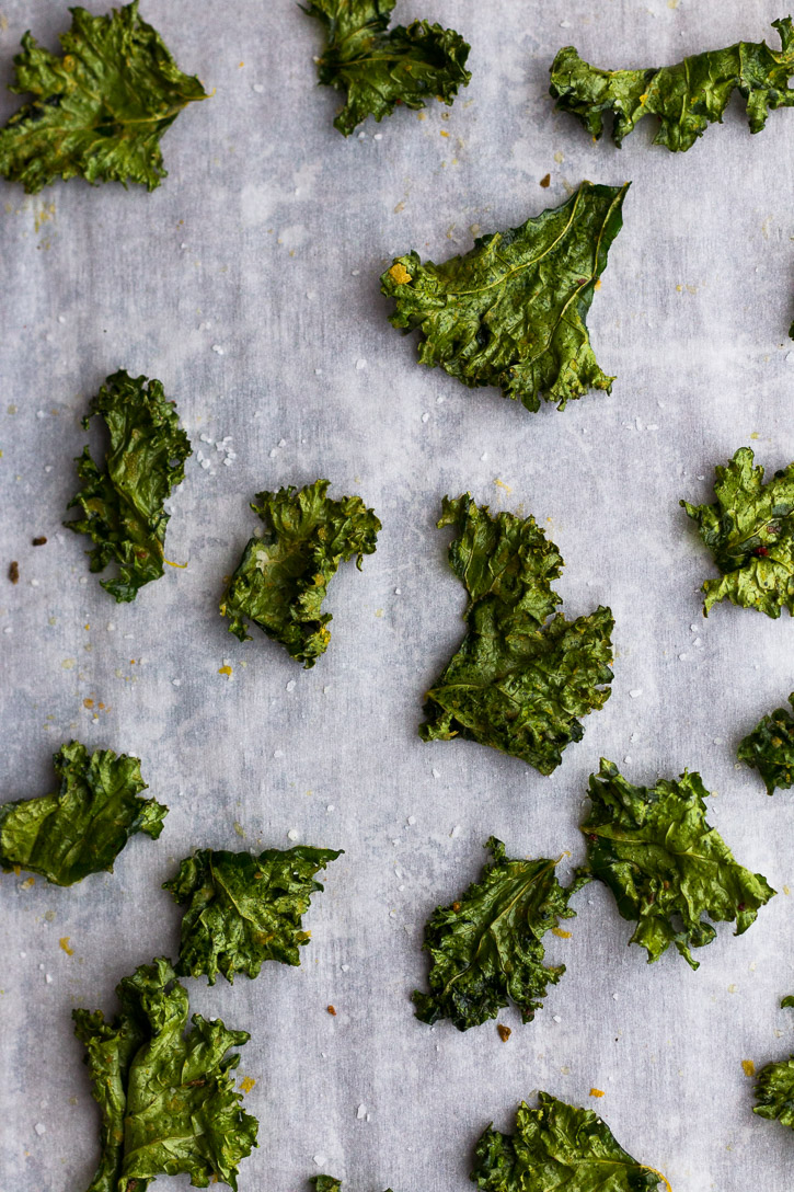 A closer view of crispy baked and seasoned kale chips on a parchment covered baking sheet.