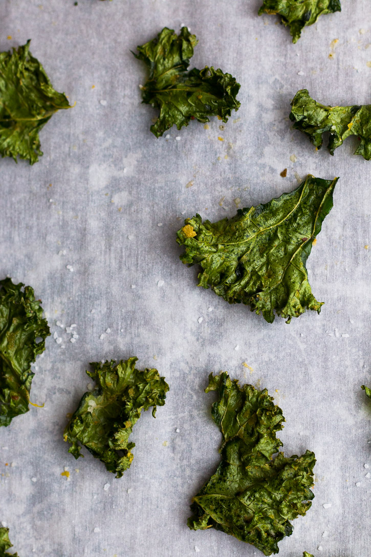 A close up of a crispy baked and seasoned kale chip on a parchment covered baking sheet.