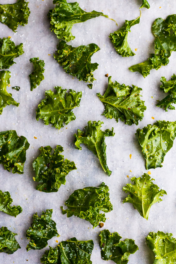 Raw and seasoned kale laid out on a parchment paper covered baking sheet.