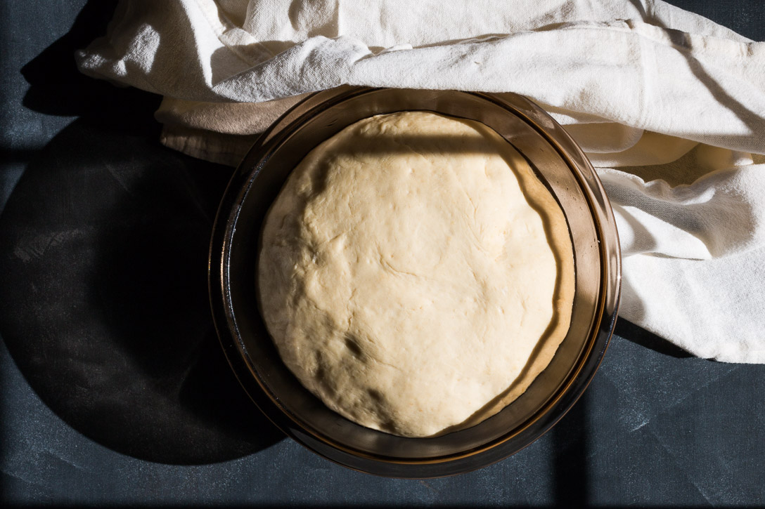 Raised and puffy dough in a glass bowl with a cloth wrapped around it.