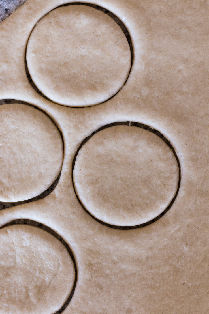 Close up overhead shot of rolled out dough with cut circles in it.