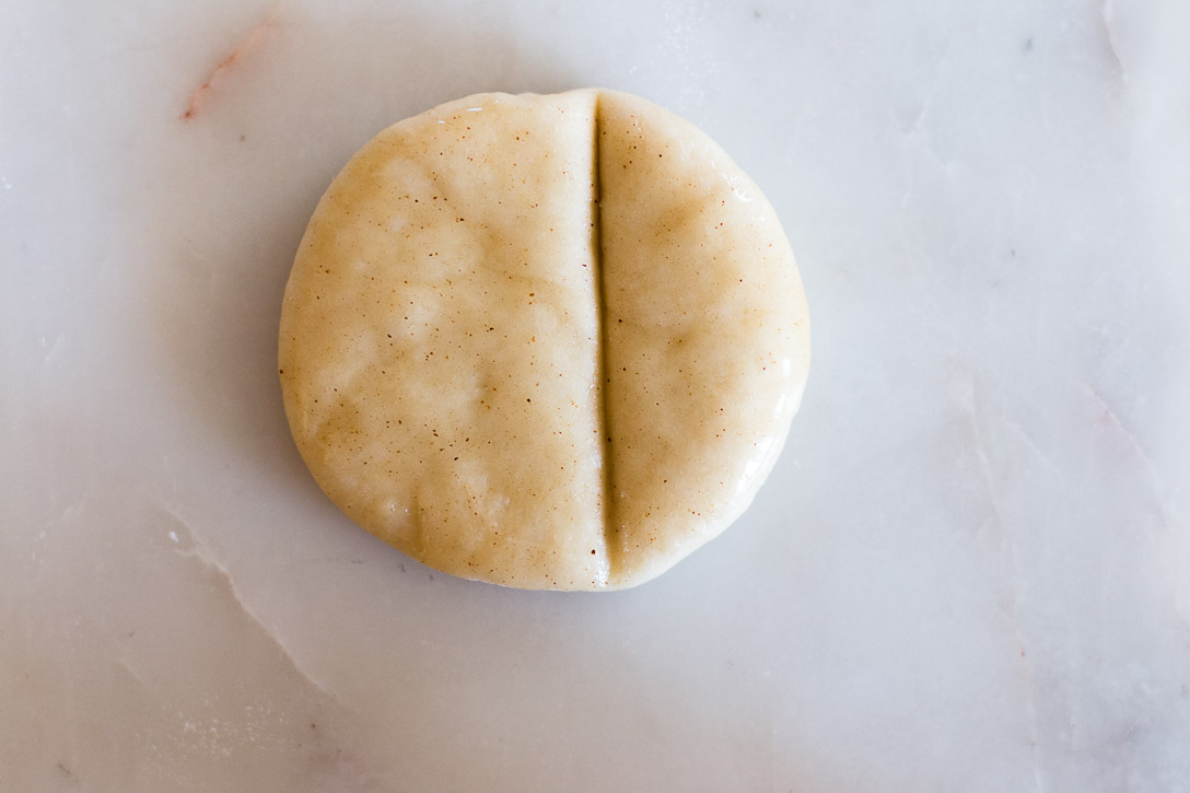 A close up of a cut circle of dough with an off-center indent on the right hand side.