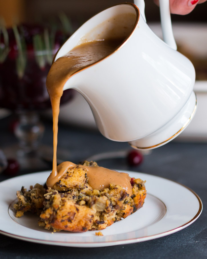 Side view of gravy from a sauce boat being poured onto a serving of plated stuffing.