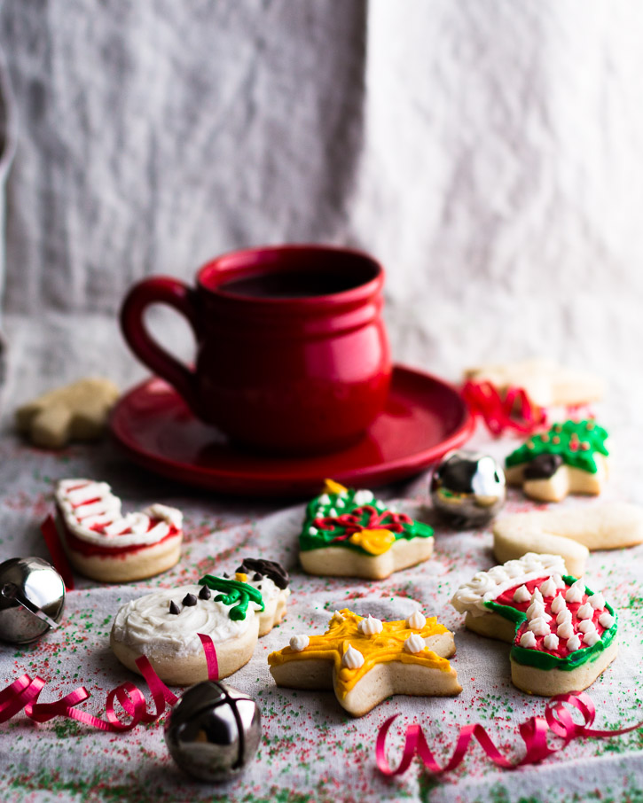 Vertical shot of frosted Christmas cookies, bells, curled ribbon, and a coffee cup and saucer.