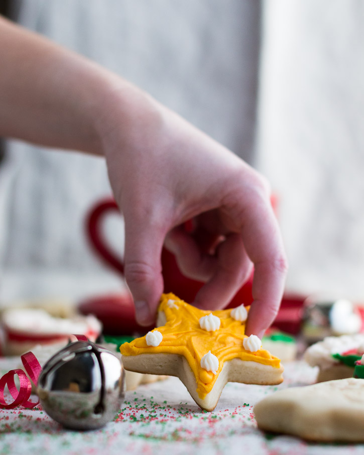 Hand holding up a frosted star shaped sour cream cookie surrounded by a bell, ribbon, and more cookies.