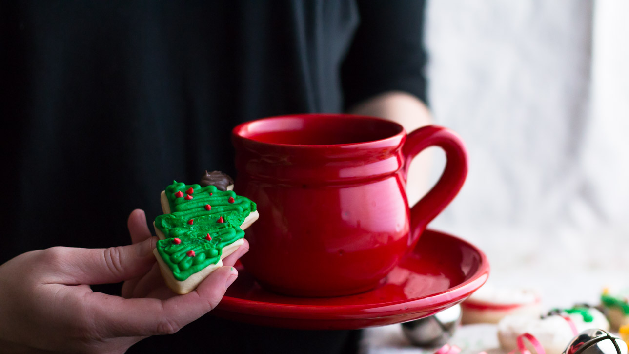 Hand holding a frosted Christmas tree shaped cookie and a coffee cup and saucer.