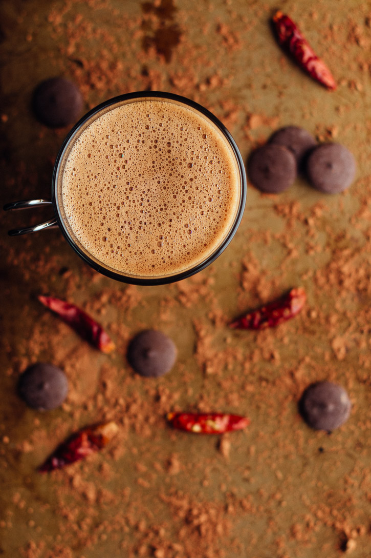 Overhead view of Spiced Mocha Hot Chocolate with Curry Paste on a cocoa covered baking sheet surrounded by chocolate wafers and dried chilies