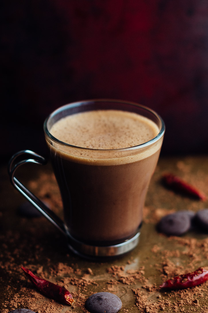 Slightly angled vertical view of glass mug with metal handle filled with hot chocolate and surrounded by cocoa powder, chocolate wafers, and dried chilies.