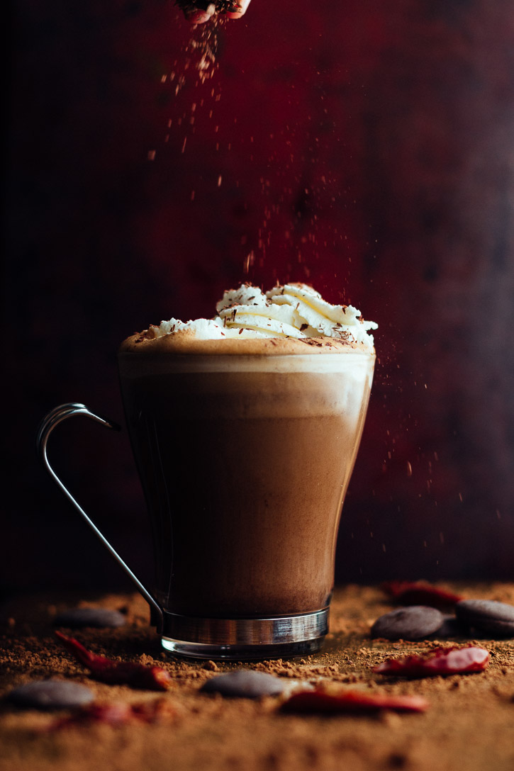 Vertical view of a Spiced Mocha Hot Chocolate with whipped cream being sprinkled with chocolate shavings.