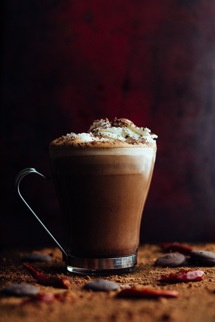 Vertical view of Spiced Mocha Hot Chocolate topped with whipped cream and chocolate shavings and surrounded by cocoa powder, chocolate wafers, and dried chilies.
