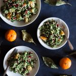 Overhead shot of three circular plates with servings of cauliflower and kale tabbouleh on a dark blue surface and surrounded by tangerines and green leaves.