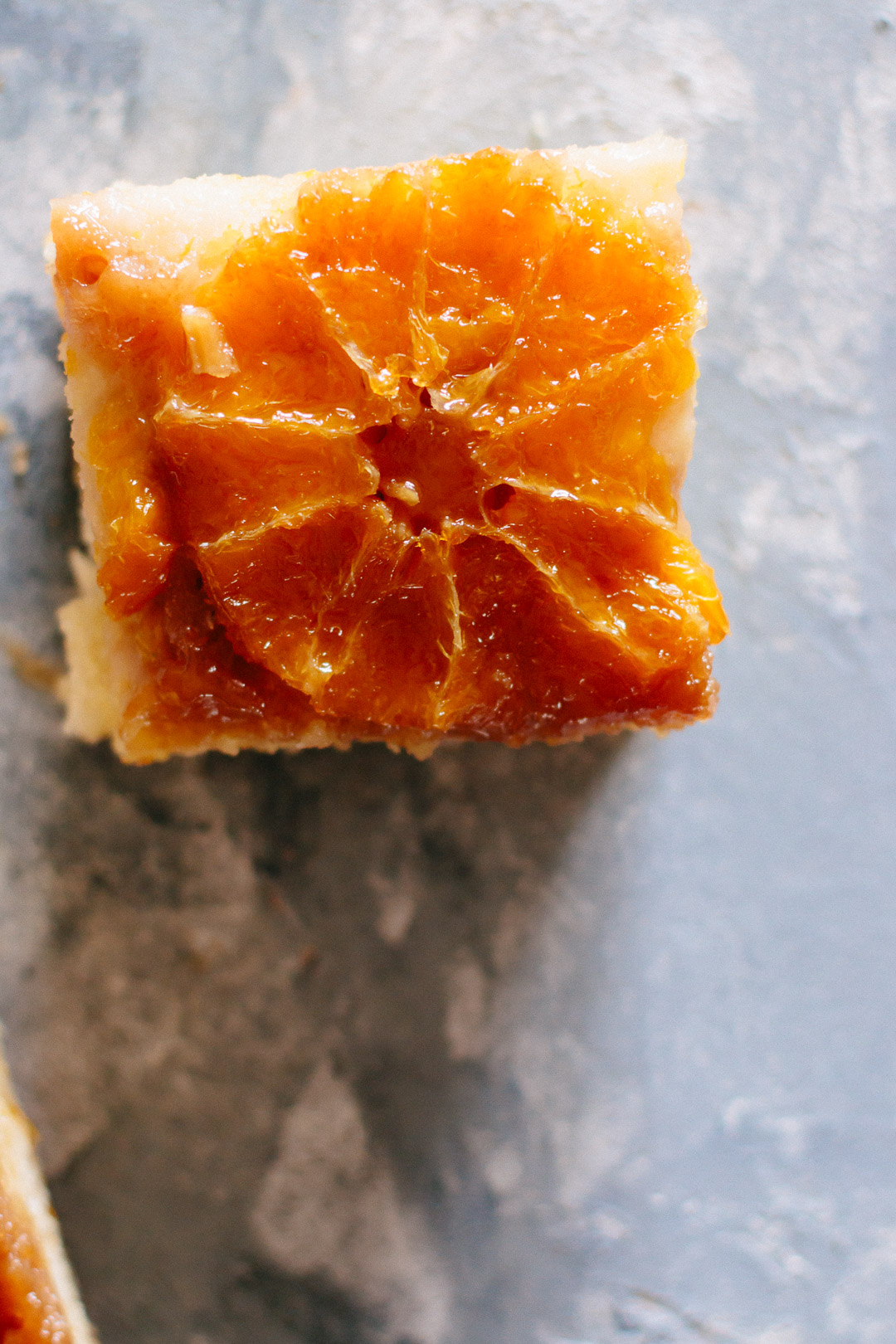 Overhead close up of a square slice of orange upside down cake.