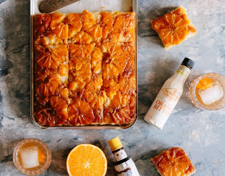 Overhead shot of cut glazed upside down cake in the sheet pan surrounded by a metal cake spatula, two orange halves, three slices of cake, an orange bitters bottle, an Angostura Bitters bottle, and two Old Fashioneds in rocks glasses.