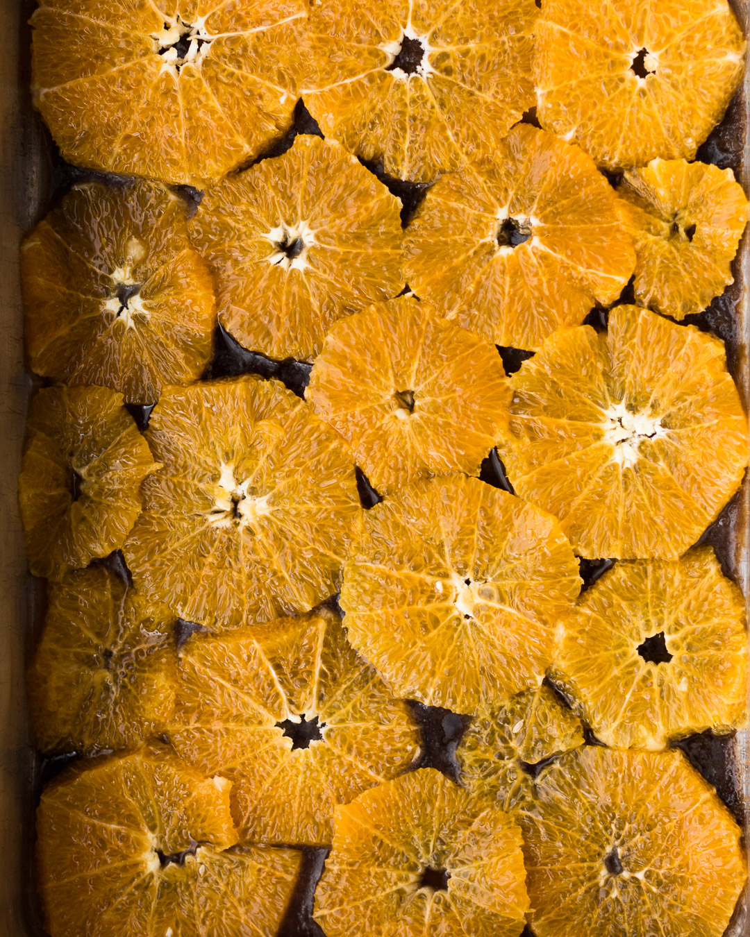 Overhead shot of raw orange slices laid out in a cake sheet pan.