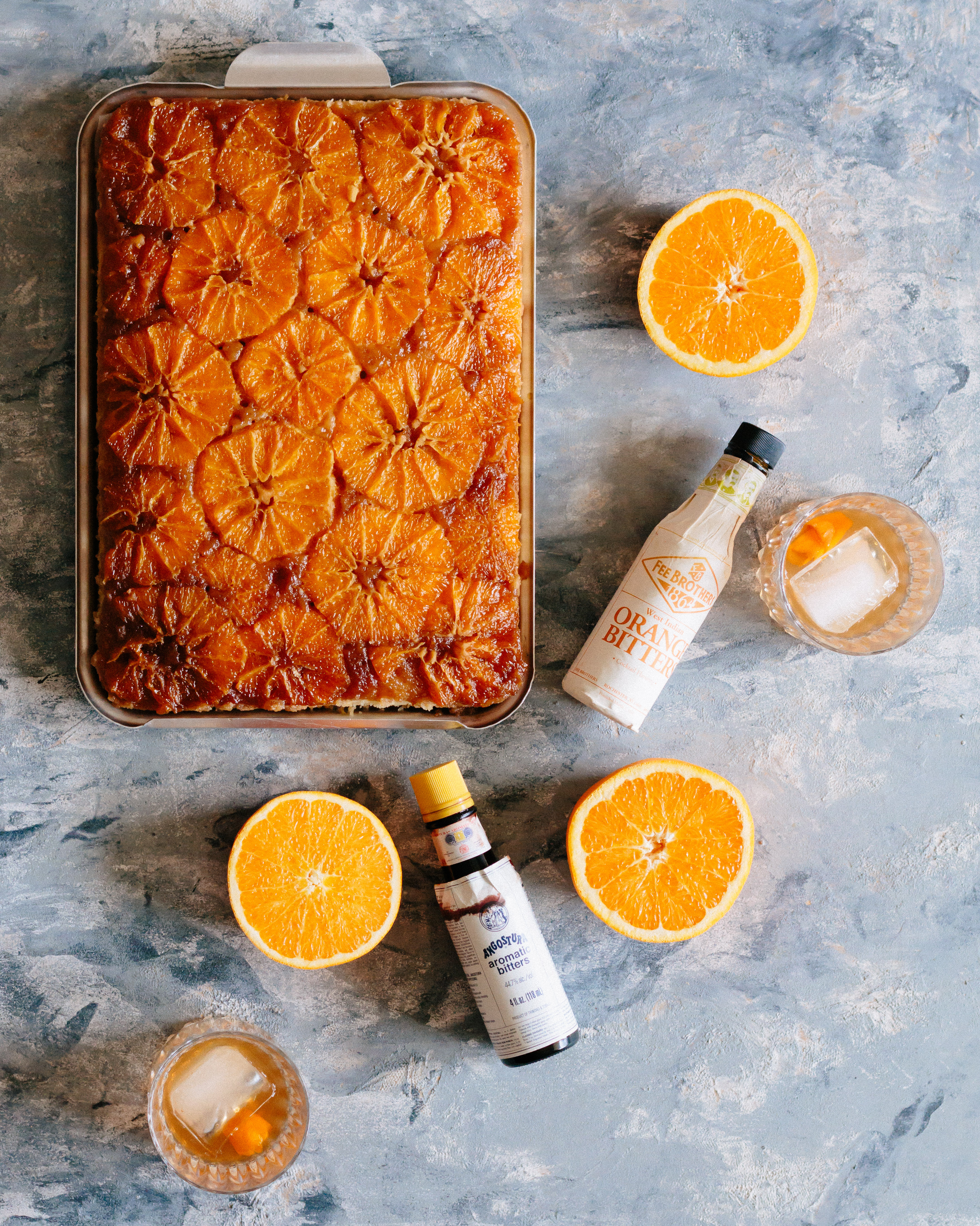 Overhead shot of uncut upside down cake still in the sheet pan surrounded by three orange halves, an orange bitters bottle, an Angostura Bitters bottle, and two Old Fashioneds in rocks glasses.