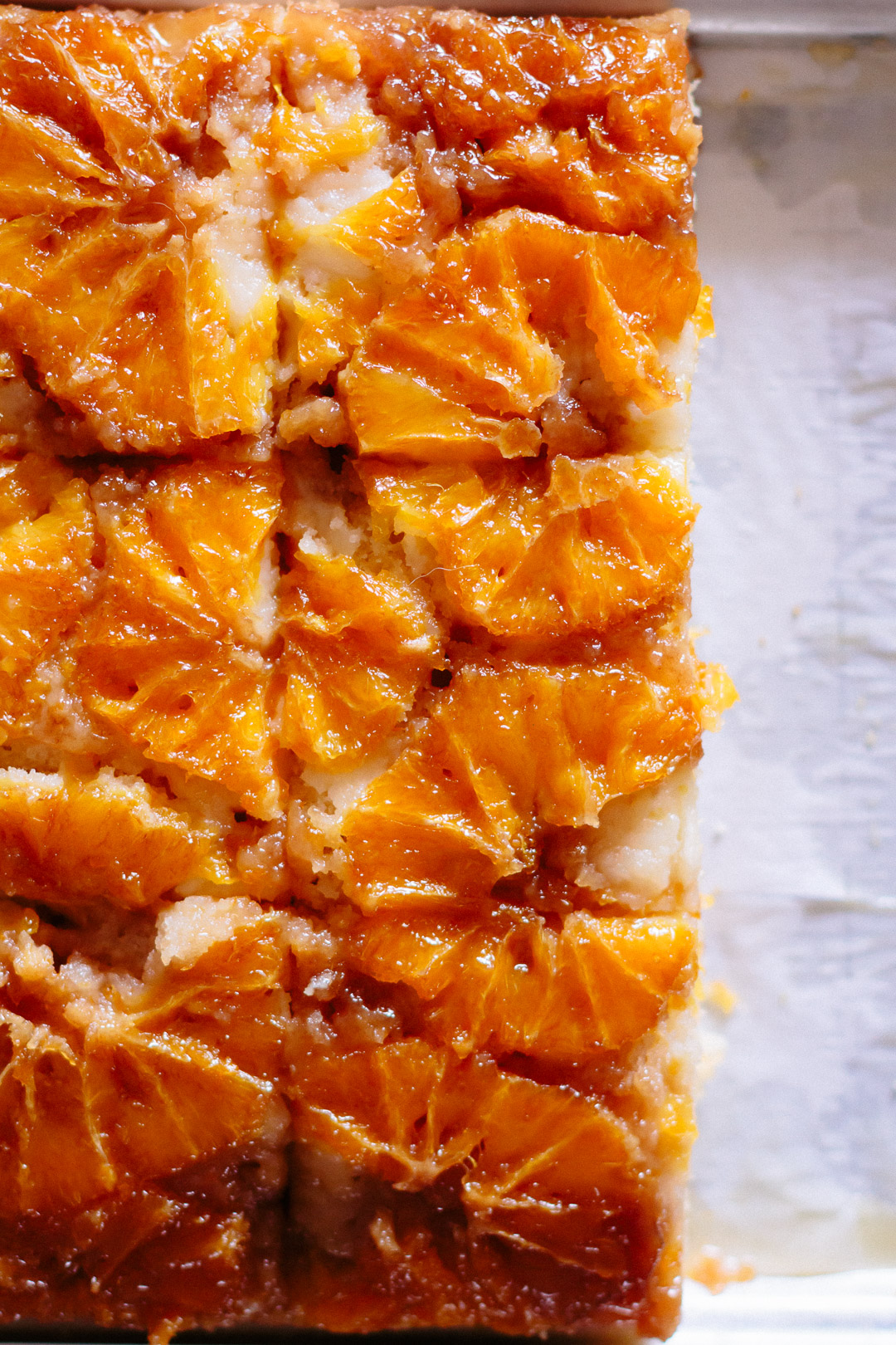 Overhead close up shot of the oranges on an upside down cake.