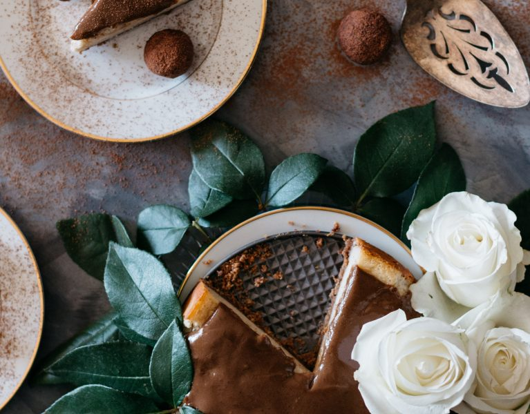 Overhead shot of a cheesecake surrounded by leaves and roses next to a plate with a cheesecake slice, truffles, and a pie server.