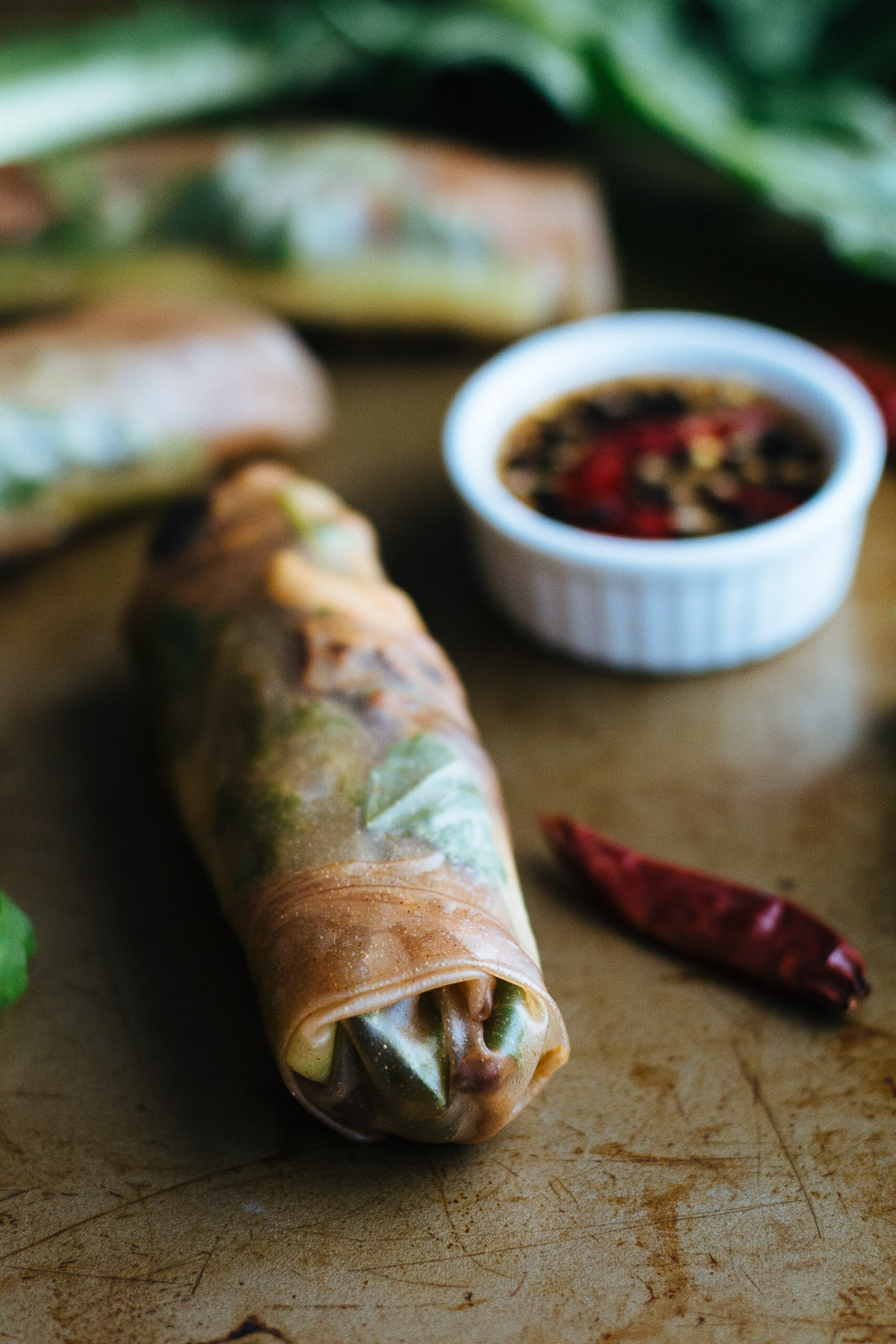 Close up angled shot of one spring roll with two spring rolls behind it along with the dipping sauce.