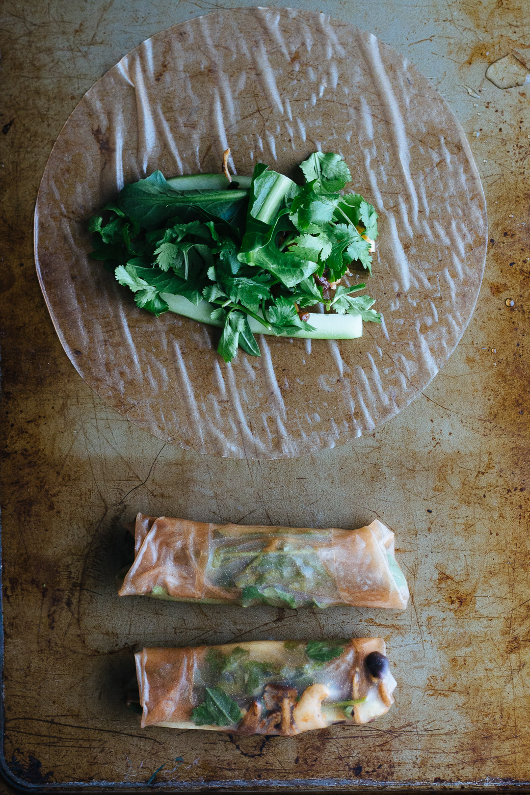 Overhead shot of two rolled spring rolls and one wet spring roll wrapper with mushrooms, cilantro, dandelion greens, and cucumbers placed in the center.