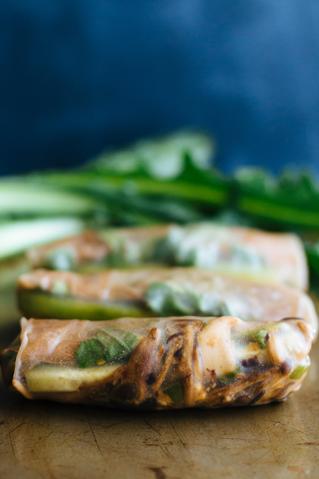 Close up vertical shot of a spring roll in front of other out of focus spring rolls and dandelion greens.