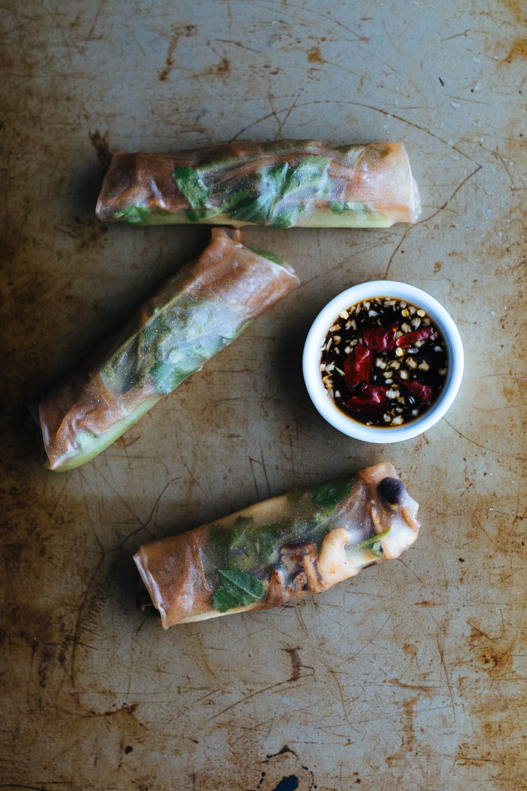 Over head shot of three wrapped spring rolls arranged around the dipping sauce on a baking sheet.