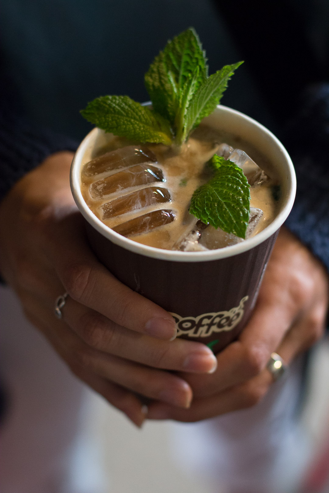 Hands holding a paper coffee cup filled with ice, mint leaves, and foamy coffee.