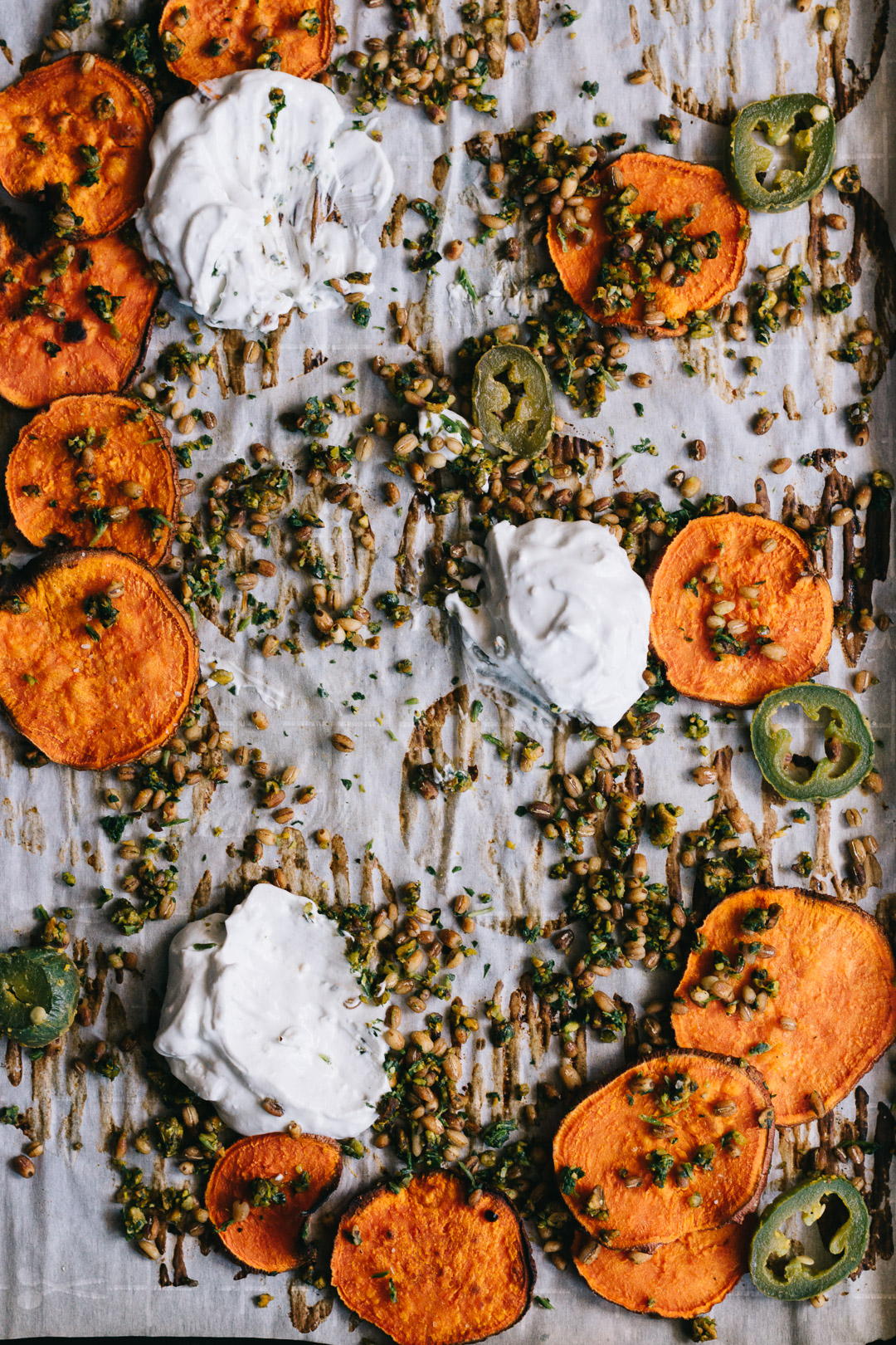 Overhead shot of parchment covered baking sheet that's been used as a serving platter people have eaten off of. There are a few sweet potato crisps leftover, gremolata and barley scattered everywhere, and dollops of dip that have been used.