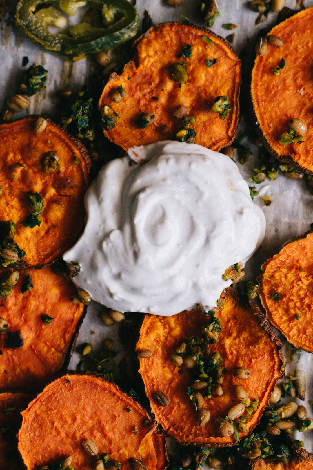 Close up overhead shot of a dollop of sour cream blue cheese dip on a parchment paper covered baking sheet surrounded by sweet potato crisps, gremolata, barley, and jalapeño slices.