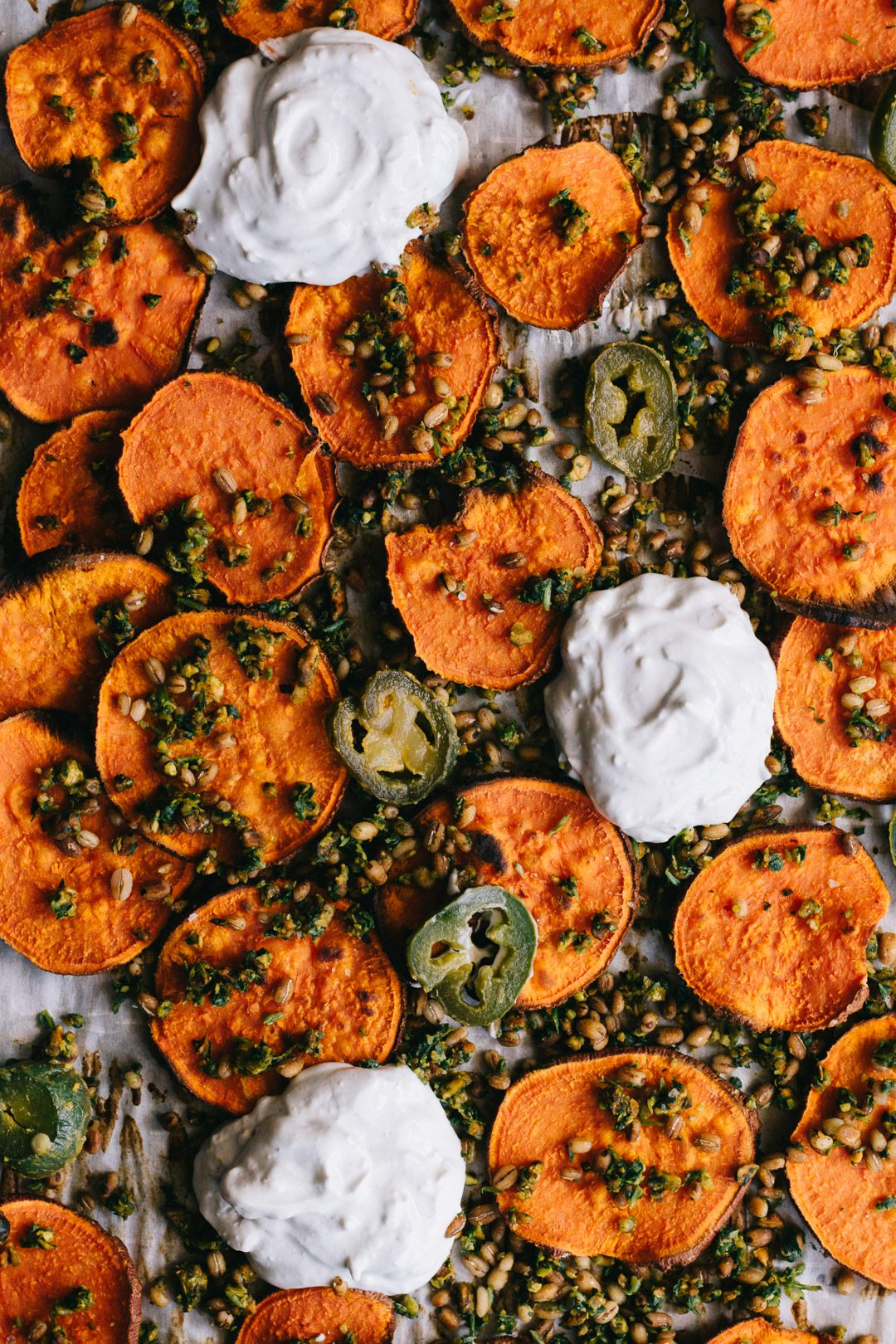 Overhead shot of three dollops of sour cream blue cheese dip on a parchment paper covered baking sheet surrounded by sweet potato crisps, gremolata, barley, and jalapeño slices.