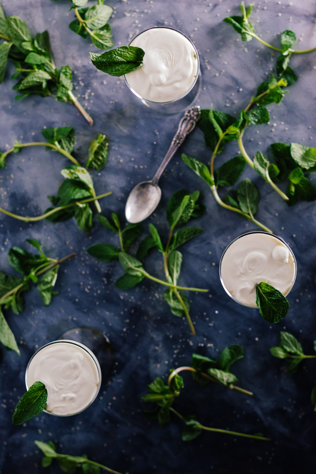 Overhead shot of three cream topped Irish Coffees surrounded by mint leaves on a smooth surface.