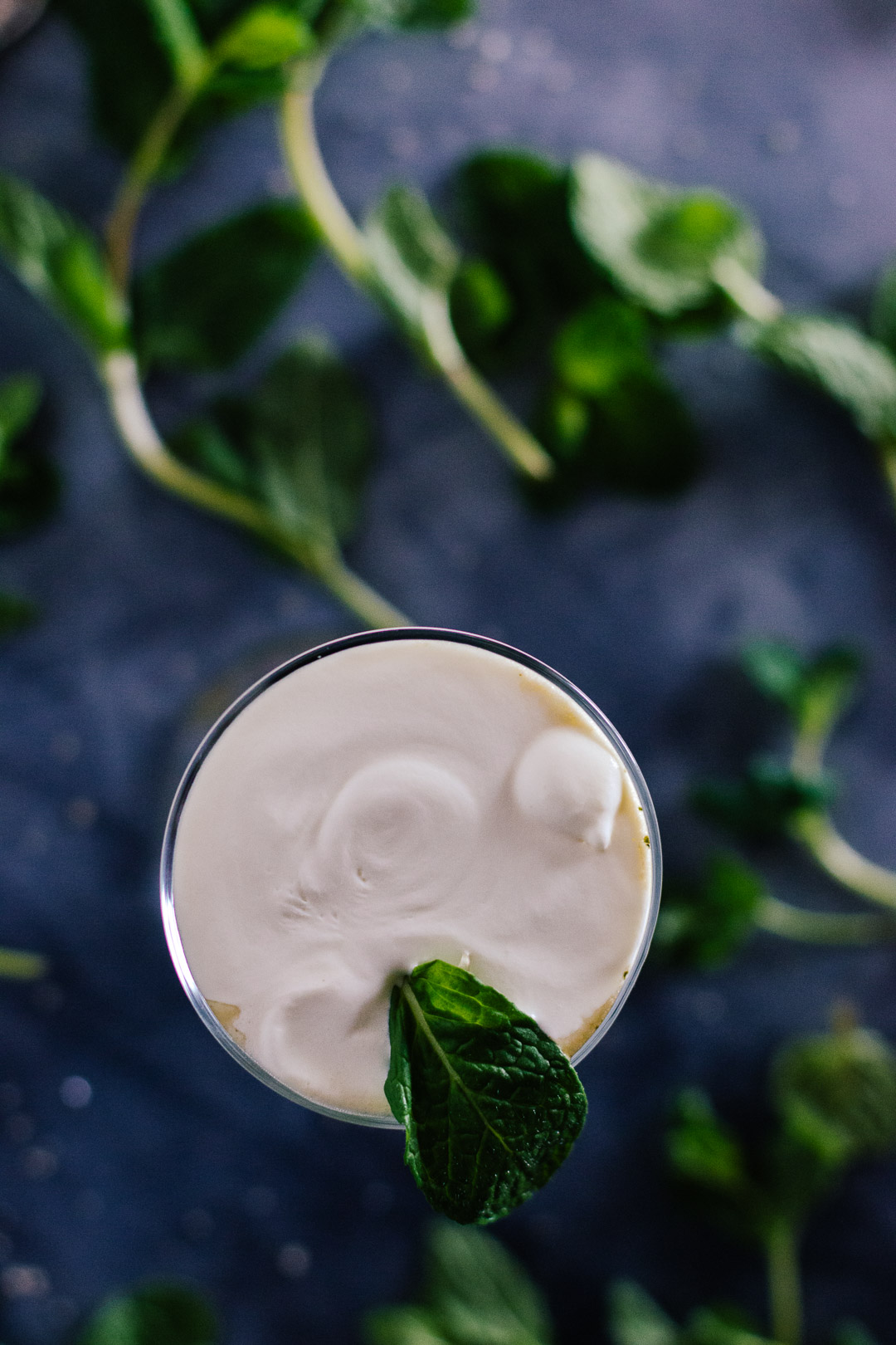 Overhead shot of cream topped Irish Coffee with a mint leave placed on top.