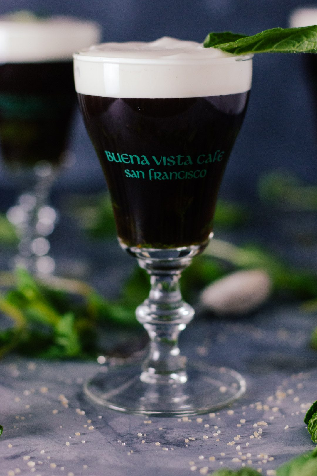 Vertical shot of an Irish Coffee topped with cream in a small glass goblet surrounded my mint leaves and grains of sugar.
