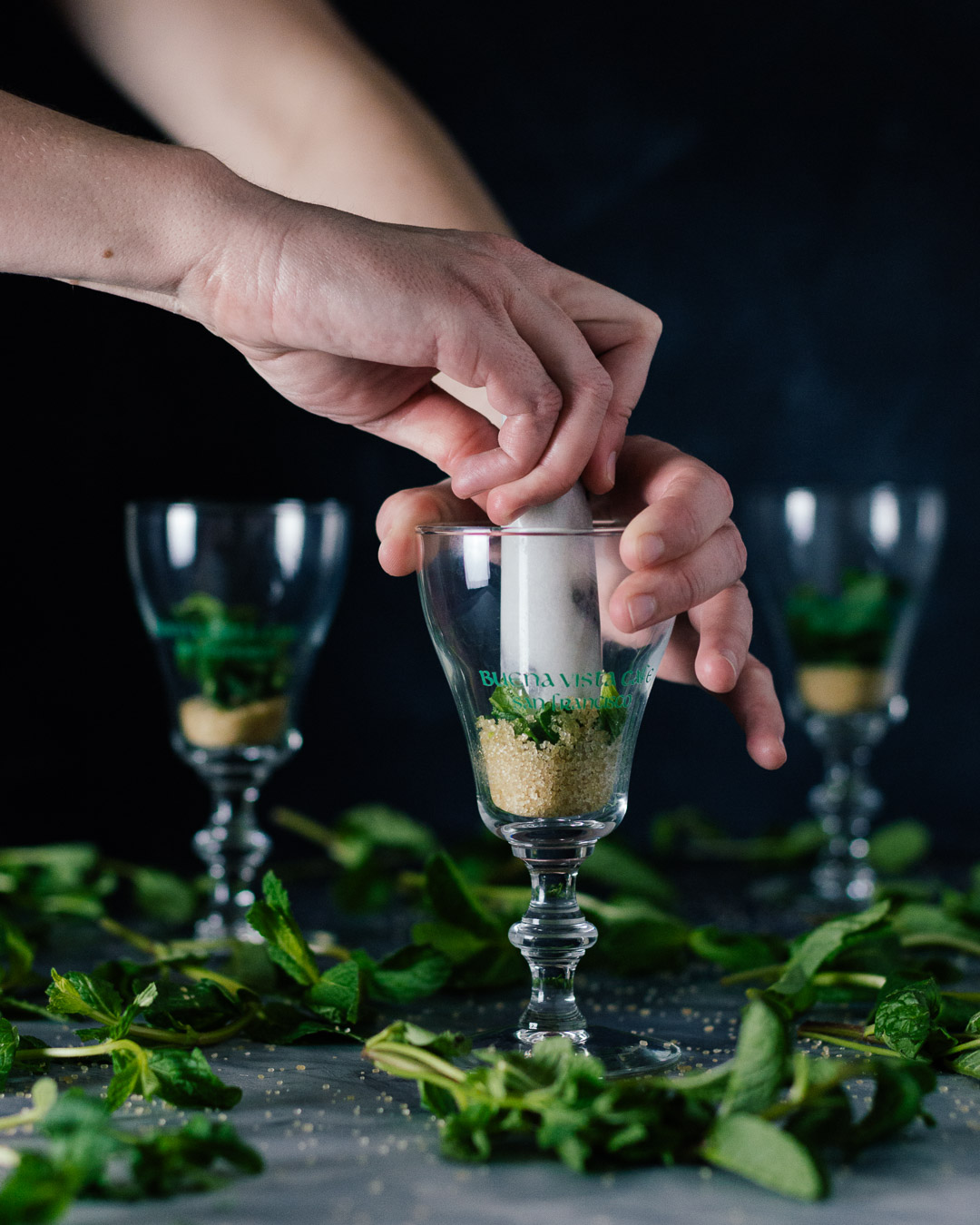 Vertical side shot of three Buena Vista Irish Coffee goblet glasses with hands muddling the mint and sugar together in the front most glass.