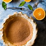 Overhead shot of a round pie on flat surface surrounded by four orange halves, two forks, and three orange leaves.