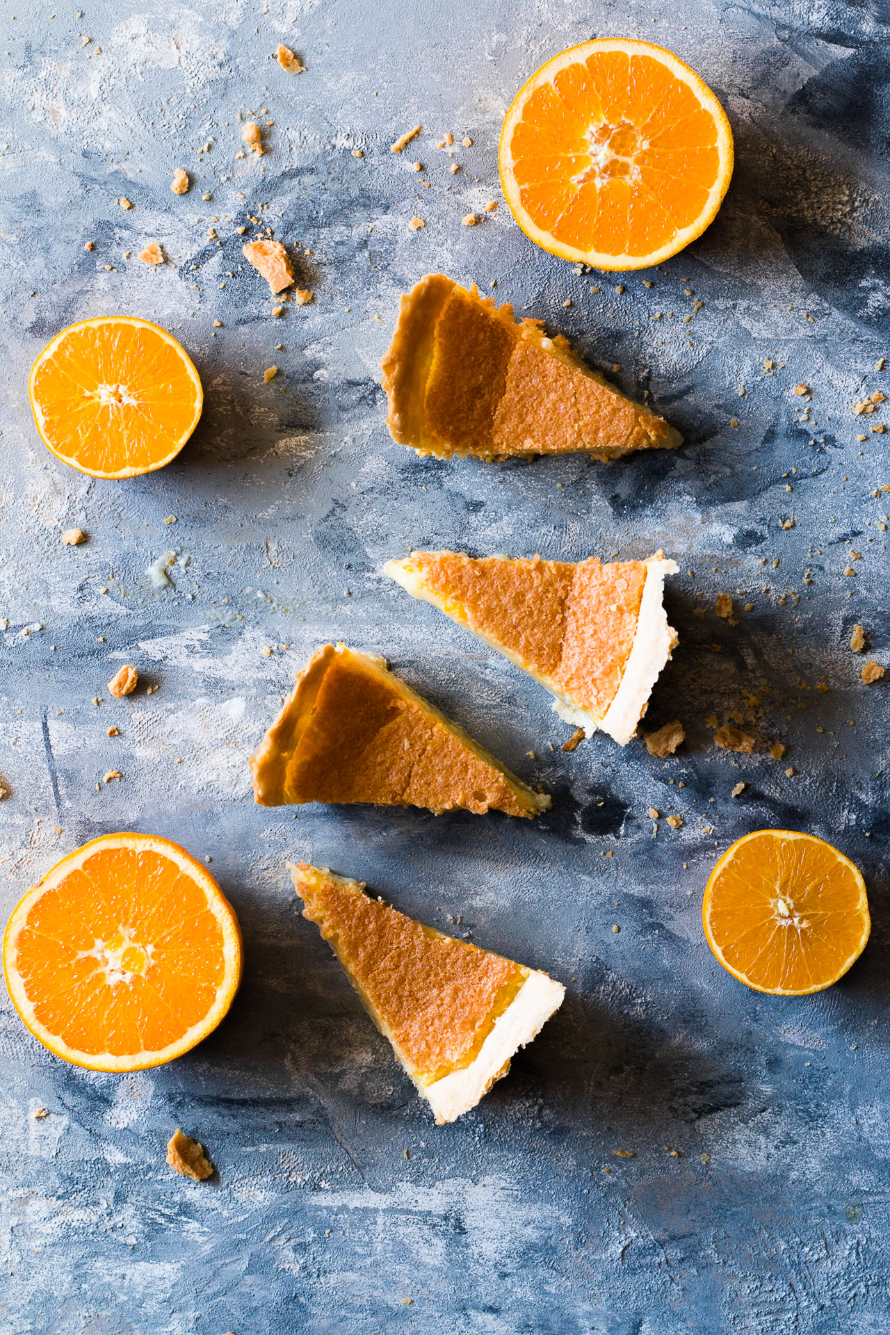 Overhead shot of four slices of pie lined up in a vertical row surrounded by four orange halves on a flat surface.